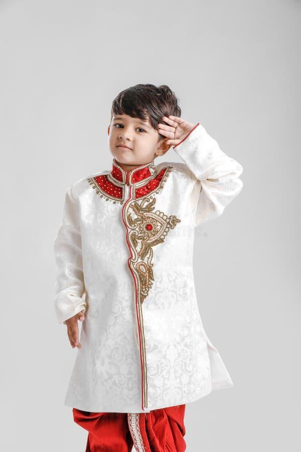 Милый индийский/азиатский мальчик в этнической носке и салютуя национальном флаге стоковая фотография rf