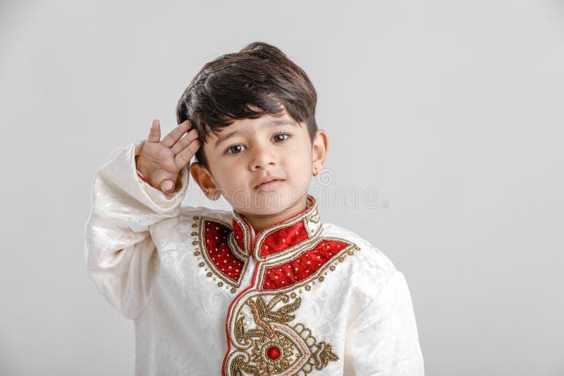 Милый индийский/азиатский мальчик в этнической носке и салютуя национальном флаге стоковые фото