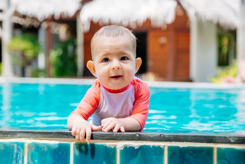 Милый и счастливый маленький младенец держит к стороне тропического бассейна и взглядам к камере и laught Младенческая девушка в  стоковые изображения