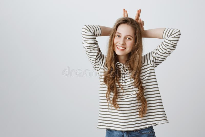 Милый как зайчик Портрет эмотивной симпатичной молодой подруги усмехаясь обширно, стоя в вскользь одеждах над серым цветом стоковое изображение rf