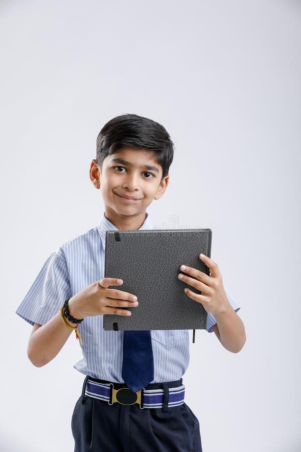 Милый маленький индийский/азиатский блокнот показа школьника над белой предпосылкой стоковое фото rf