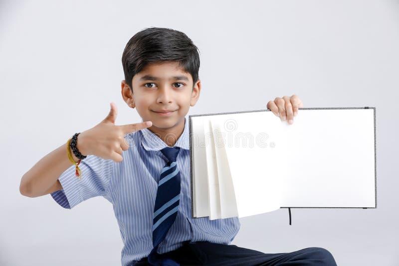 Милый маленький индийский/азиатский блокнот показа школьника над белой предпосылкой стоковая фотография