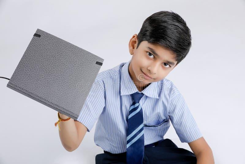 Милый маленький индийский/азиатский блокнот показа школьника над белой предпосылкой стоковые изображения rf