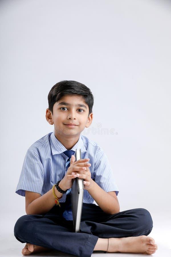 Милый маленький индийский/азиатский школьник с книгой чтения зрелищ над белой предпосылкой стоковое изображение