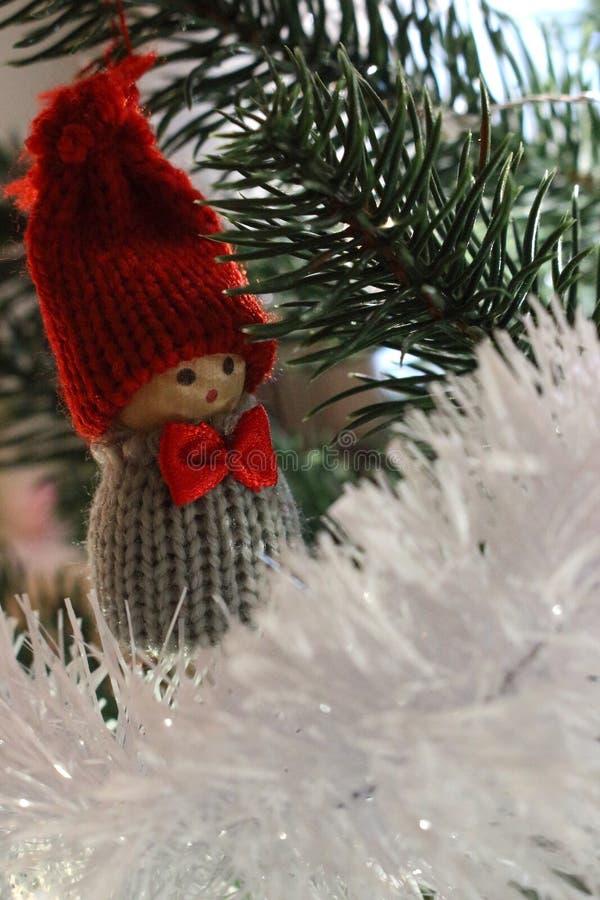 Милый маленький карлик с красной шляпой на рождественской елке Рождественская елка с игрушкой мальчика и белой гирляндой Празднич стоковые фото
