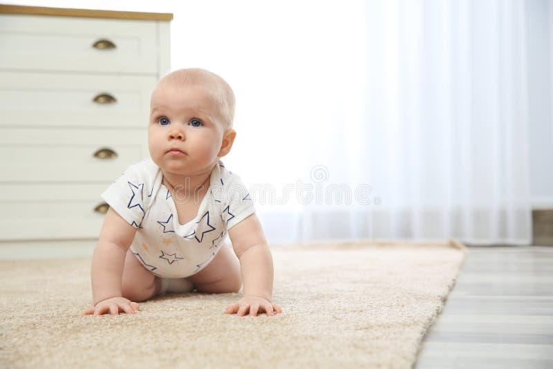 Милый маленький младенец вползая на ковре внутри помещения стоковое изображение rf