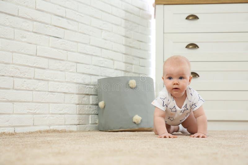Милый маленький младенец вползая на ковре стоковые изображения rf