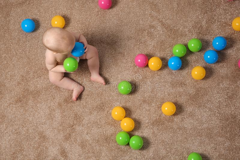 Милый маленький младенец вползая на ковре с игрушками стоковая фотография rf