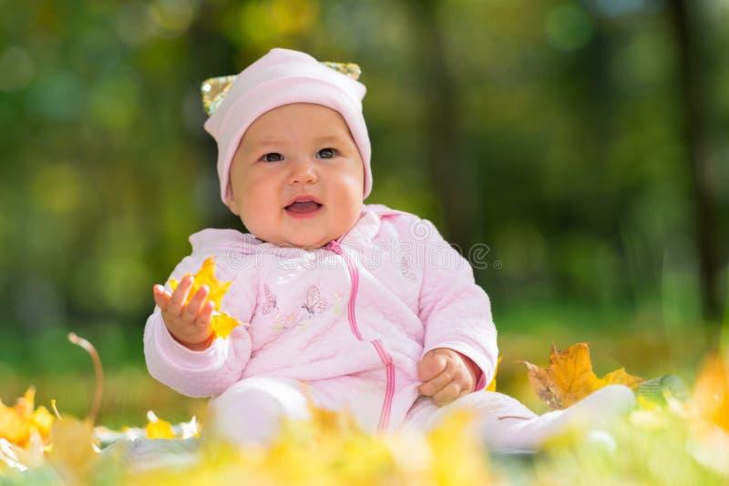 Милый маленький ребенок в пинке в парке осени стоковое изображение