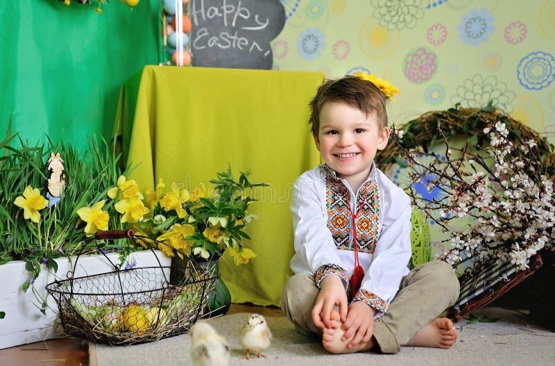 Милый маленький ребенок усмехаясь празднующ пасху 2 всех пасхального яйца принципиальной схемы цыпленока ведра цветут детеныши по стоковое фото rf