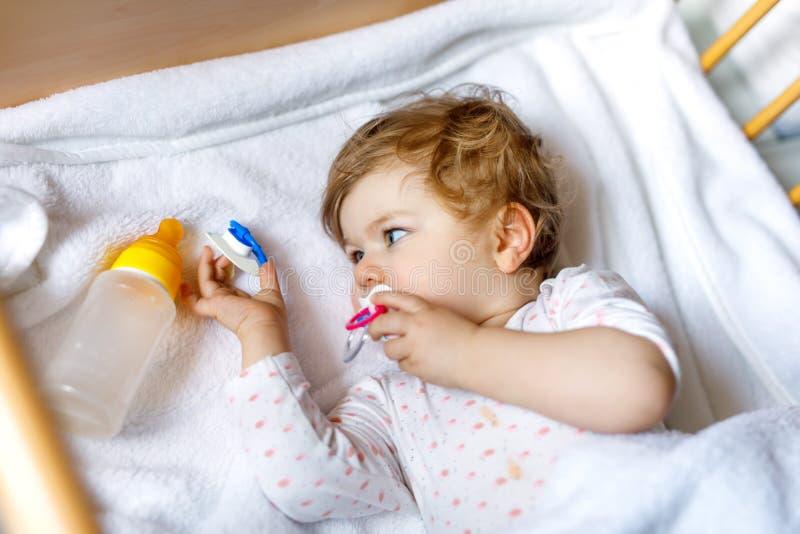 Милый маленький ребёнок держа бутылку с формулой слабый и выпивать Ребенок в кровати кроватки младенца перед спать стоковые фотографии rf