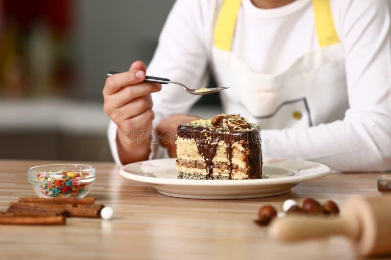 Милый маленький шеф-повар с вкусным десертом в кухне, крупном плане стоковое изображение rf