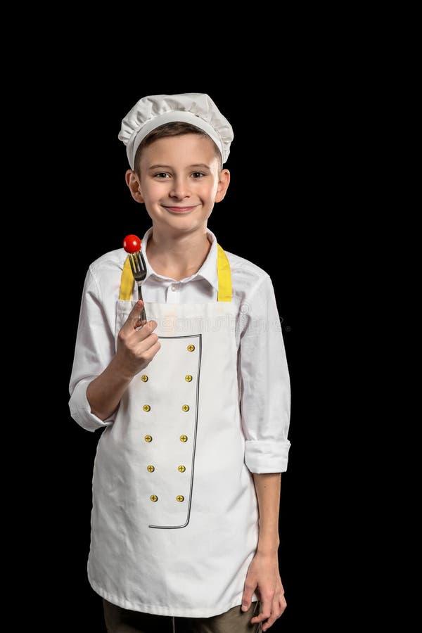 Милый маленький шеф-повар с томатом на вилке против темной предпосылки стоковое фото