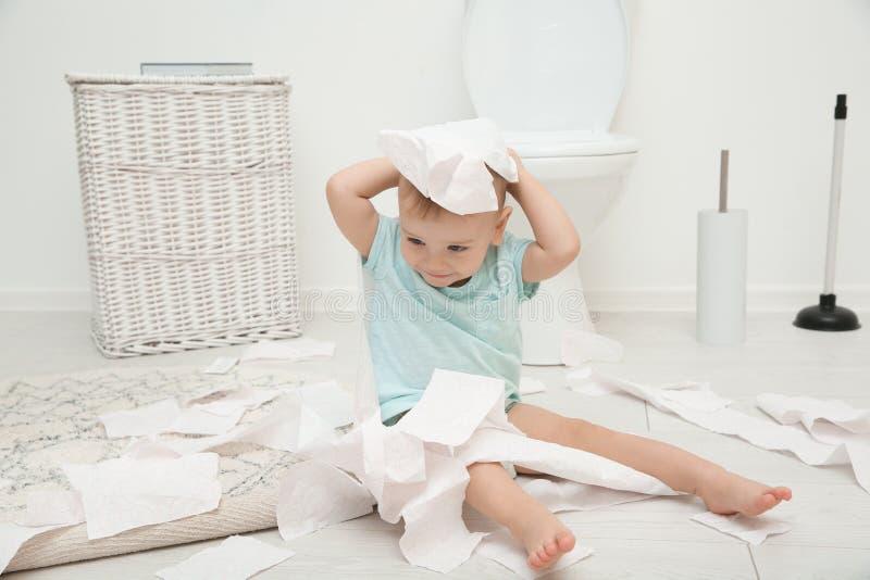 Милый малыш играя с туалетной бумагой стоковое фото rf