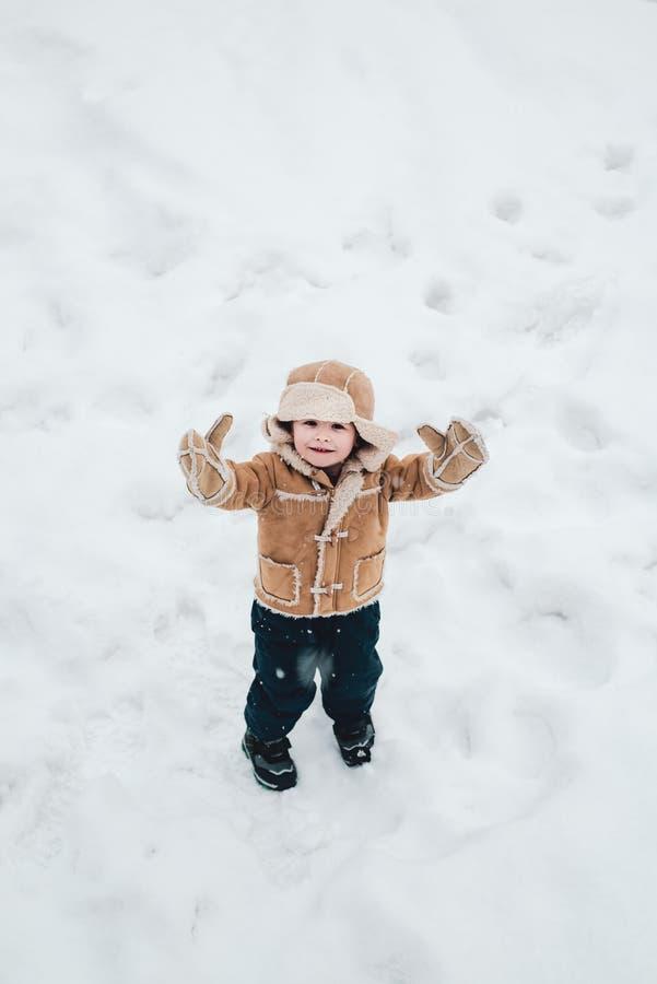 Милый мальчик в одеждах зимы Делать снежный ком и потеху зимы для детей Счастливый ребенок играя со снегом на снежной зиме стоковая фотография