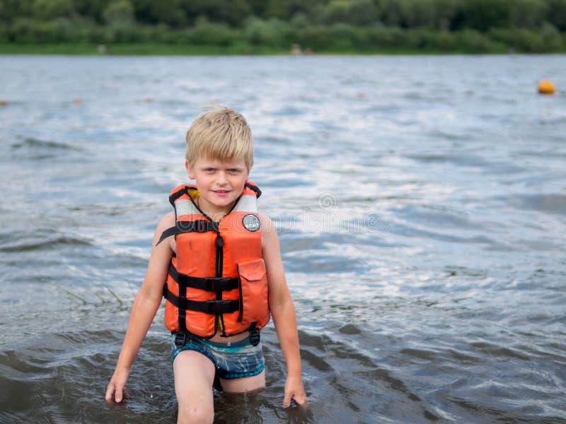 Милый мальчик в оранжевом заплывании спасательного жилета в реке стоковое фото rf
