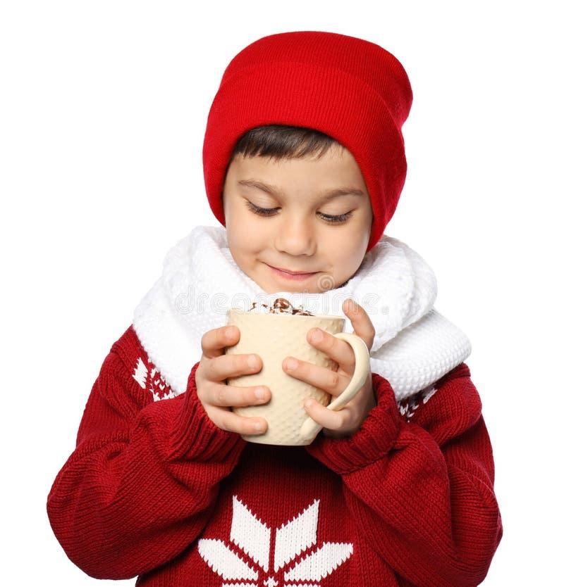 Милый мальчик в теплых одеждах и с чашкой горячего напитка какао на белой предпосылке стоковые изображения