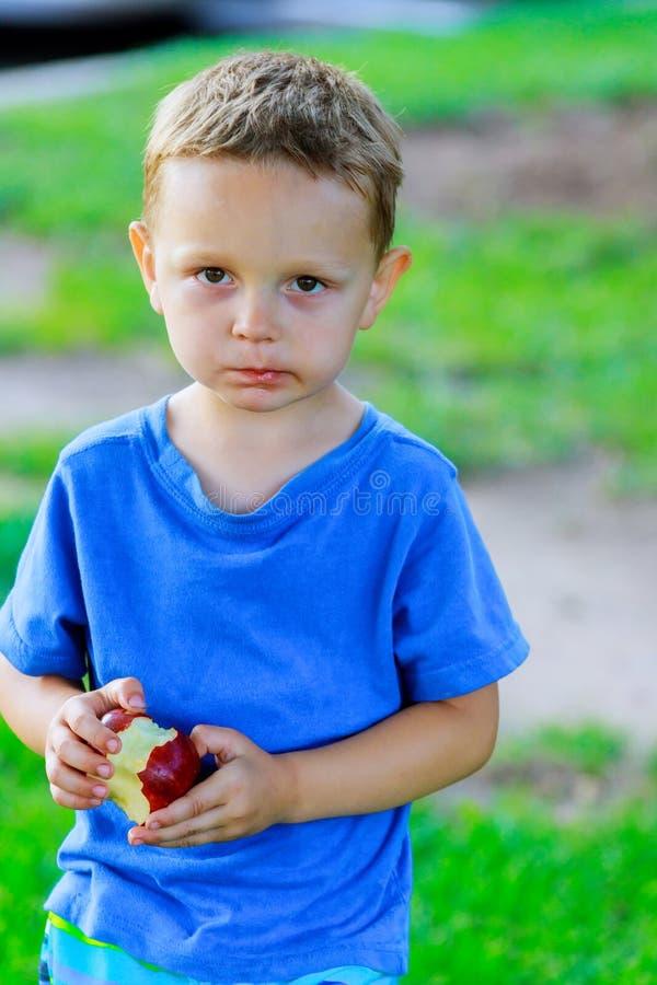 Милый мальчик есть красное яблоко в зеленом парке стоковые фотографии rf