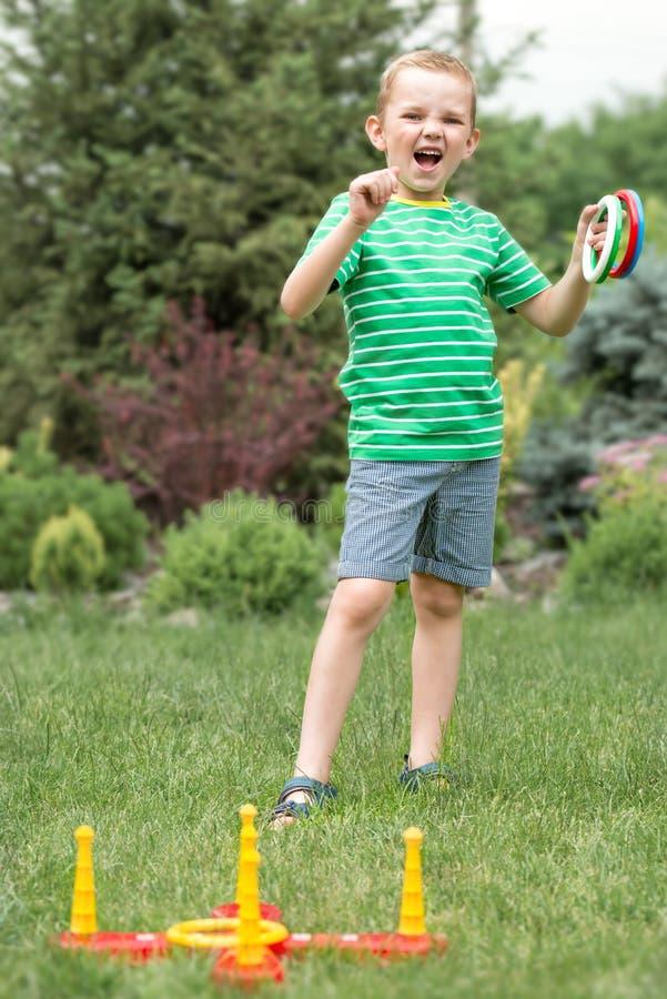 Милый мальчик играя кольца игры бросая outdoors в парке лета Утеха победы стоковое фото