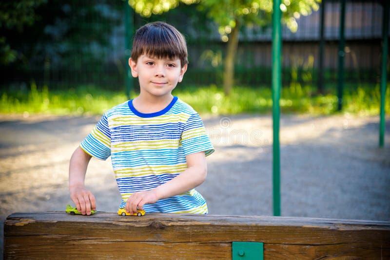 Милый мальчик, играя с маленькими автомобилями игрушки на улице на заходе солнца, летнее время стоковые фото