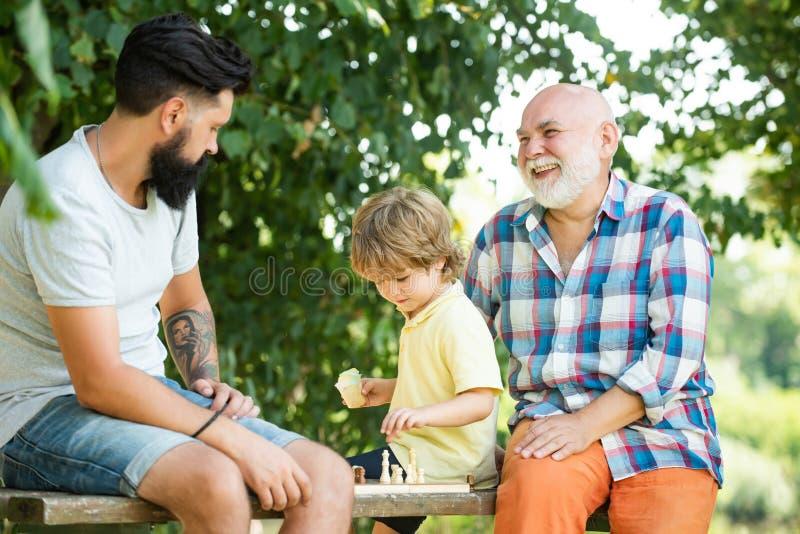Милый мальчик играя шахматы с родителями Поколение людей и этапы расти вверх Мужская Multi семья поколения стоковые изображения