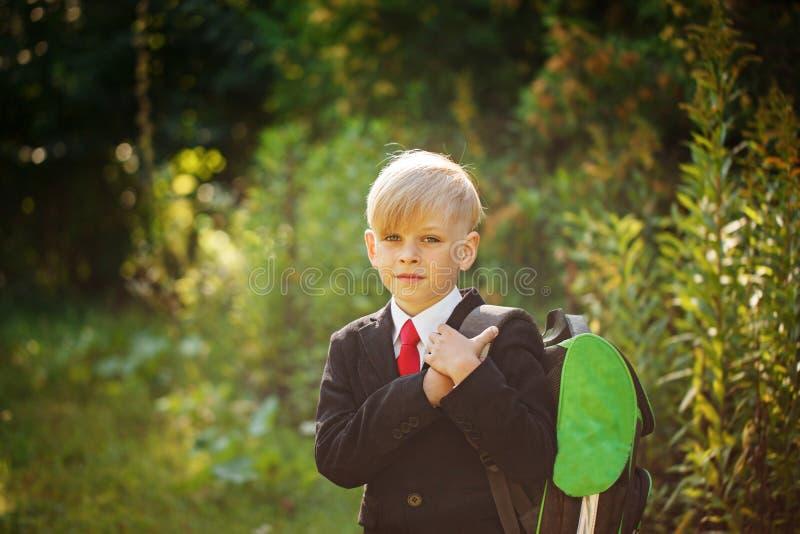 Милый мальчик идя назад к школе Мальчик в костюме Ребенок с рюкзаком на первый учебный день стоковая фотография rf