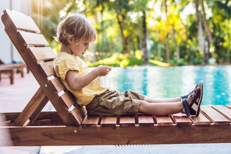 Милый мальчик использует smartphone лежа на deckchair мимо стоковые изображения