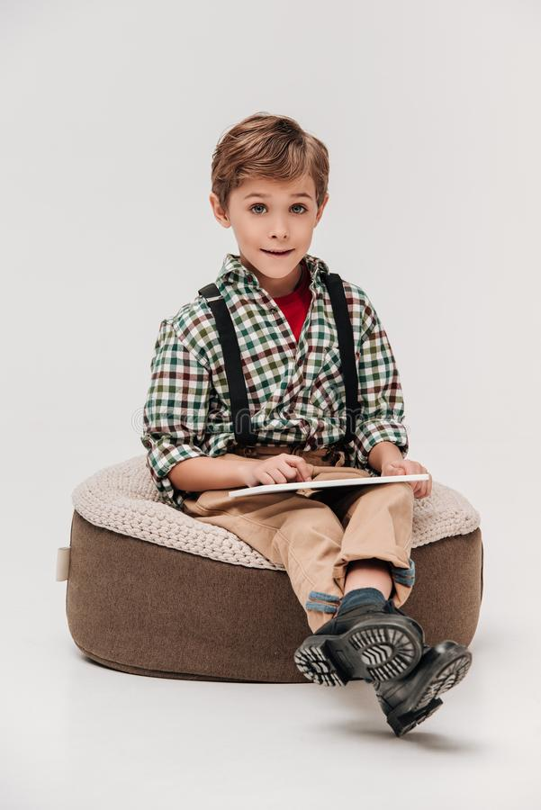 милый мальчик используя цифровую таблетку и усмехающся на камере стоковые фотографии rf