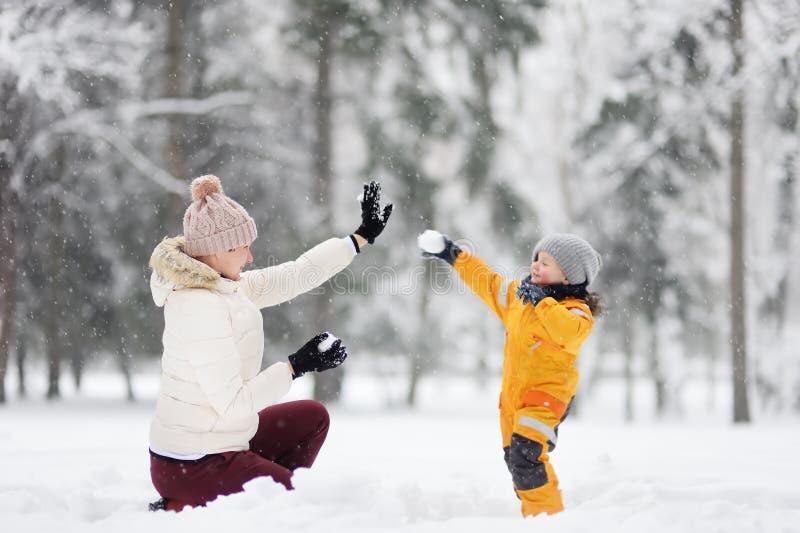 Милый мальчик и бабушка/няня/мать играя снежные комья в парке зимы стоковая фотография rf