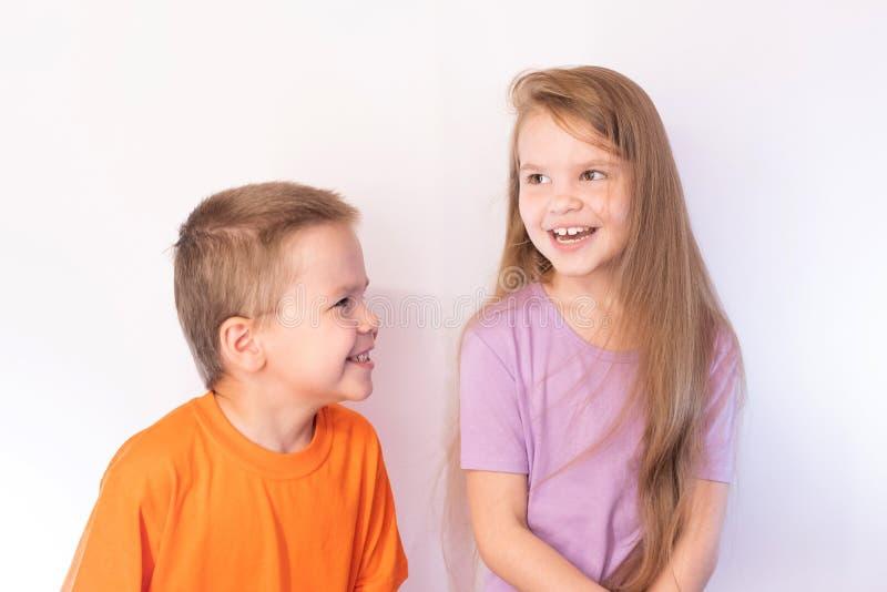 Милый мальчик и девушка, потеха, смеясь, на светлой предпосылке стоковая фотография