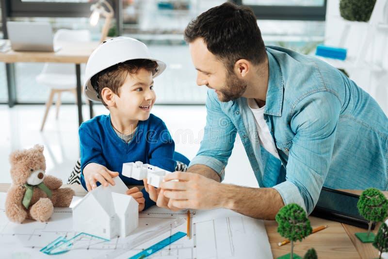 Милый мальчик и его сын обсуждая 3D расквартировывают модель стоковые фотографии rf