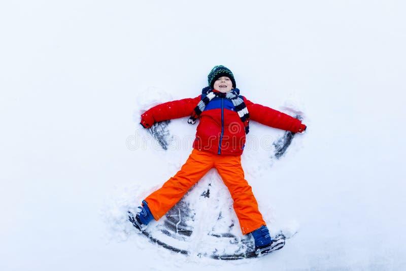 Милый мальчик маленького ребенка в красочной зиме одевает делать ангела снега, кладя вниз на снег стоковое фото rf