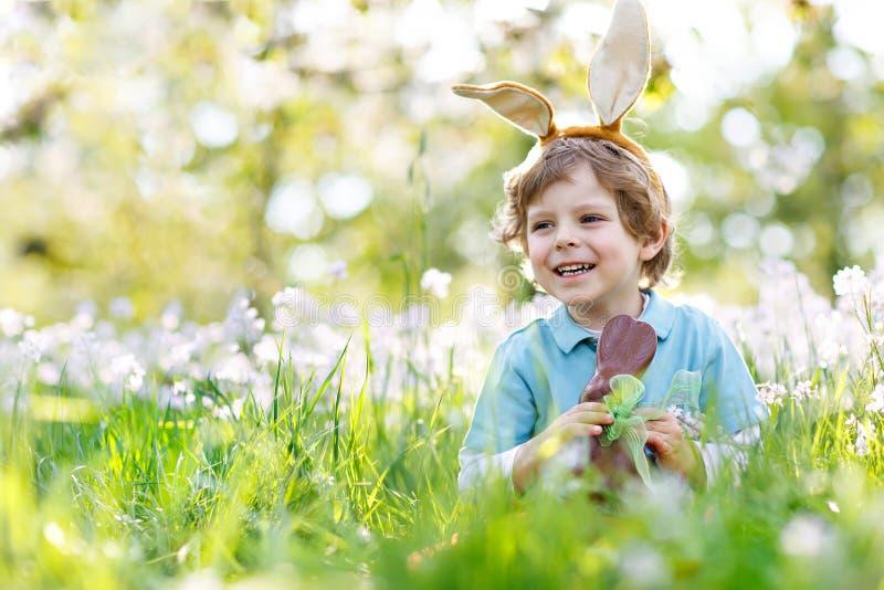 Милый мальчик маленького ребенка с ушами зайчика пасхи празднуя fugure кролика шоколада еды ребенка традиционного пиршества счаст стоковые фото