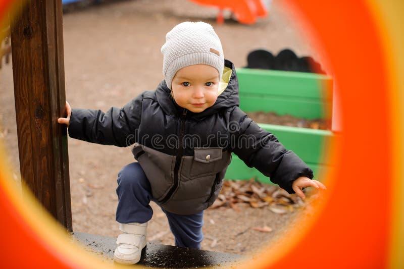Милый мальчик одел в теплых одеждах и шляпе идя на p стоковое фото