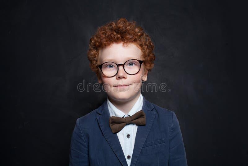 Милый мальчик ребенка в костюме и бабочка в классе на предпосылке доски стоковое изображение rf