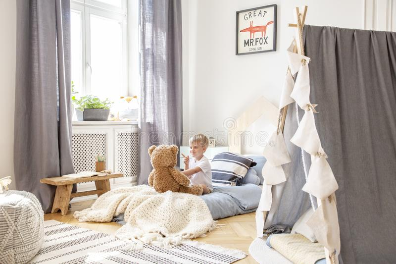 Милый мальчик сидя в удобной кровати играя с плюшевым мишкой, реальным фото естественного интерьера игровой стоковые изображения rf