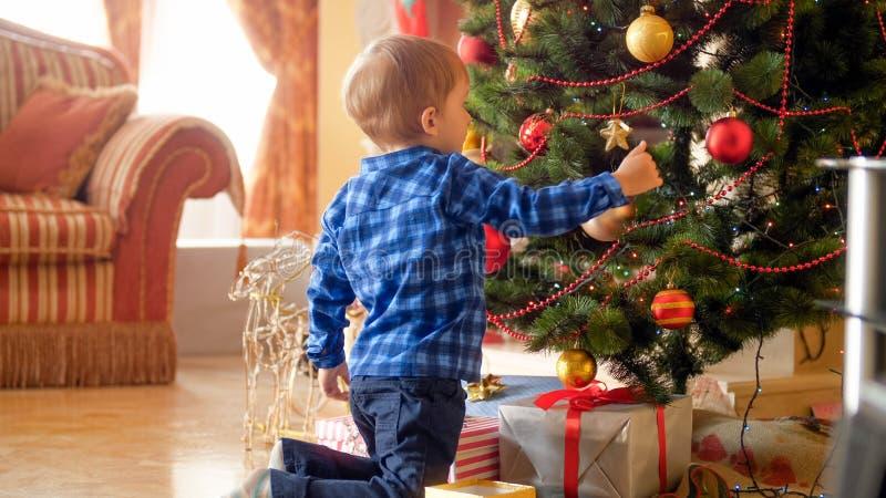 Милый мальчик сидя под рождественской елкой и украшая его с безделушками стоковое фото