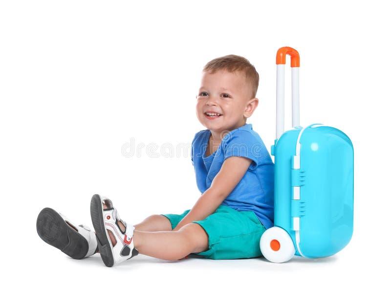 Милый мальчик с голубым чемоданом на белизне стоковые изображения rf