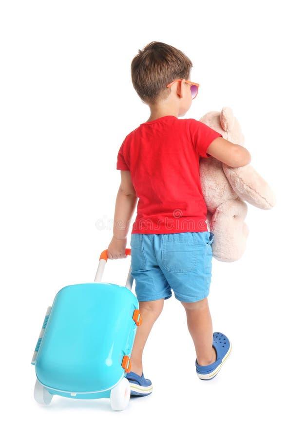 Милый мальчик с игрушкой и голубым чемоданом на белизне стоковые изображения