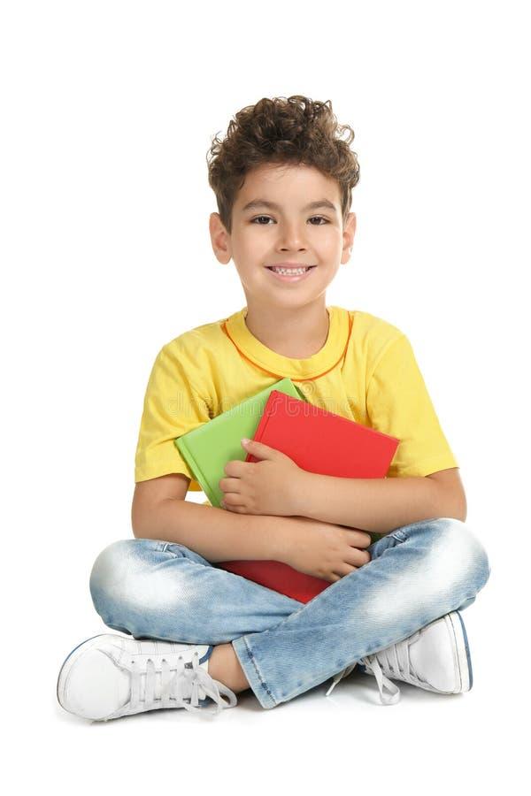 Милый мальчик с книгами на белой предпосылке стоковые фотографии rf
