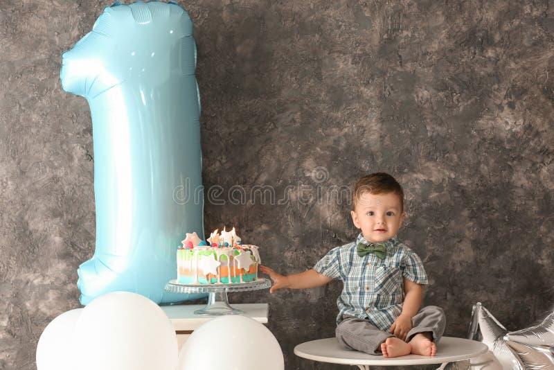 Милый мальчик с очень вкусным тортом сидя на таблице в комнате украшенной для первого дня рождения стоковая фотография