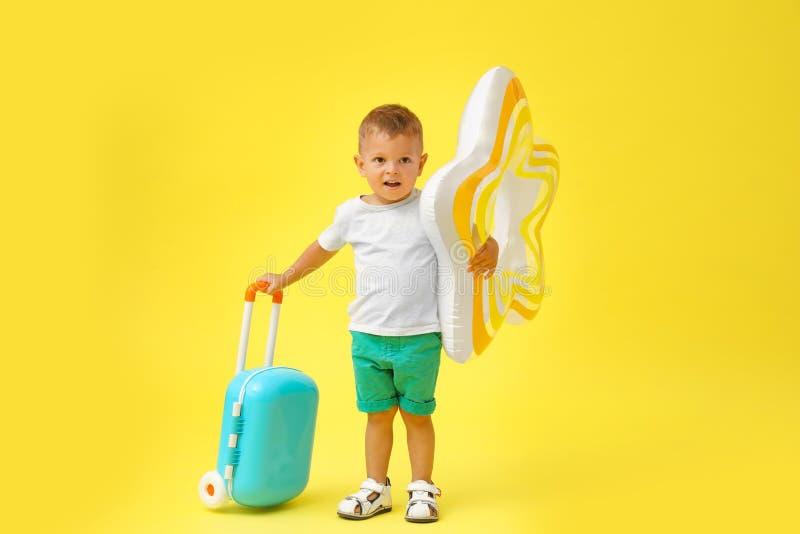 Милый мальчик с раздувным кольцом и голубым чемоданом стоковая фотография rf