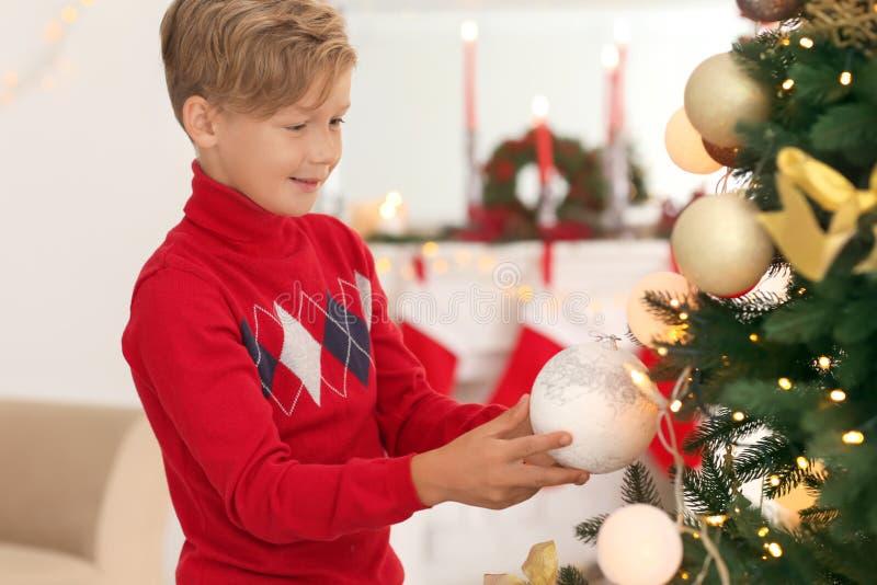 Милый мальчик украшая рождественскую елку дома стоковая фотография