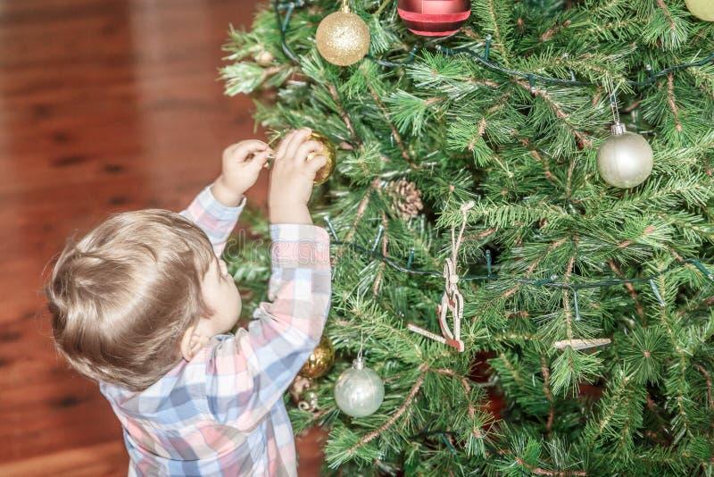 Милый мальчик устанавливает декоративный шарик на большой рождественской елке стоковые фотографии rf