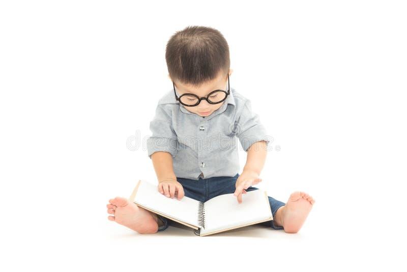 Милый меньшая детская игра с книгой и нося стеклами пока сидящ на поле над белой предпосылкой стоковое фото