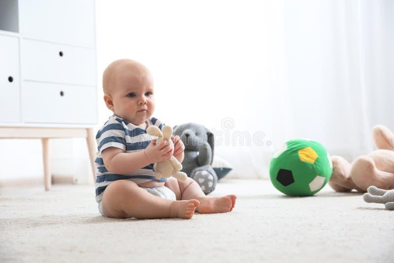Милый меньший младенец на ковре Вползая время стоковые изображения