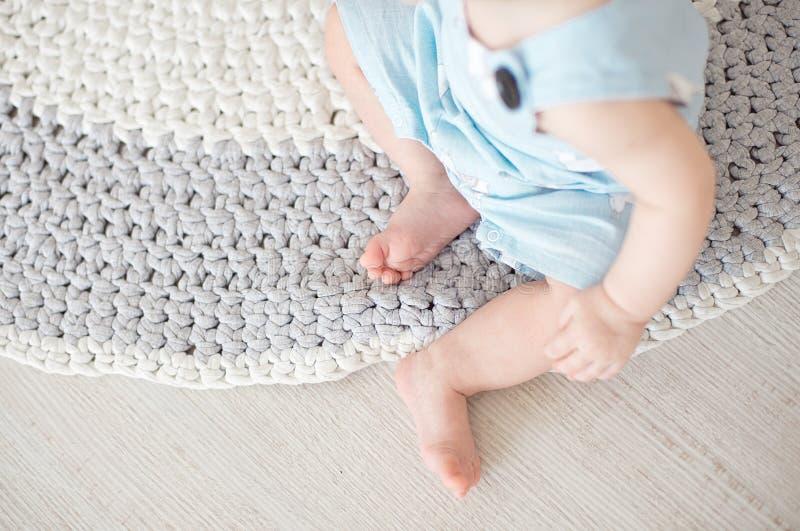 Милый младенец в голубых прозодеждах сидит на связанном ковре стоковые фотографии rf