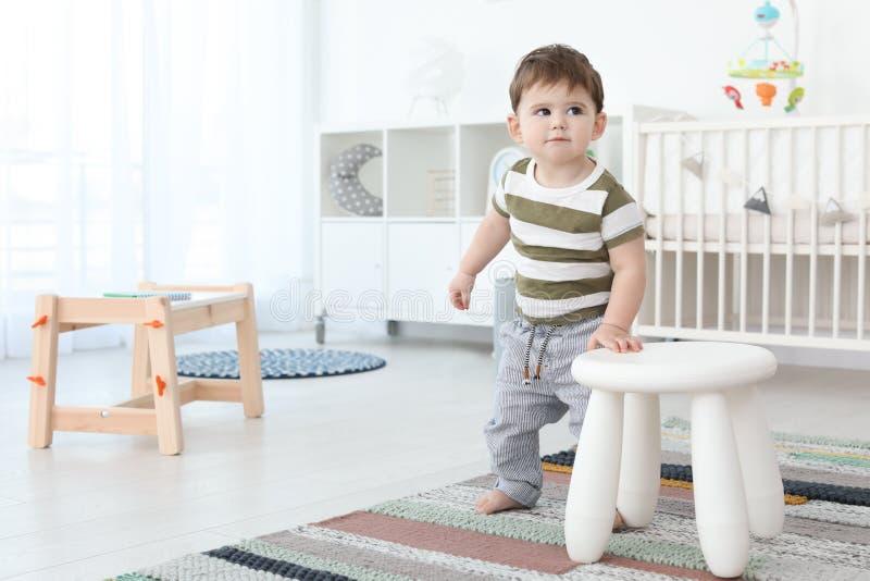 Милый младенец держа дальше для того чтобы stool дома стоковые изображения
