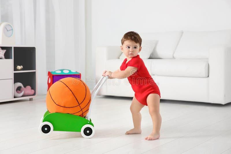 Милый младенец играя с ходоком и шариком игрушки стоковые изображения
