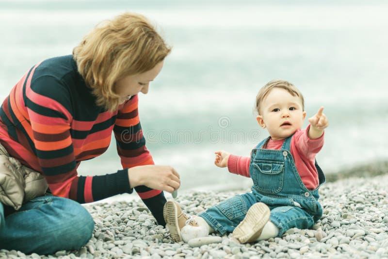 Милый младенец и его мать играя с камешками на пляже стоковая фотография